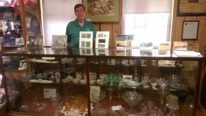 Jerry Long, president of the Gas City Historical Society, shows off colored glass dinnerware manufactured at the end of the 19th century by the U.S. Glass Factory in Gas City.